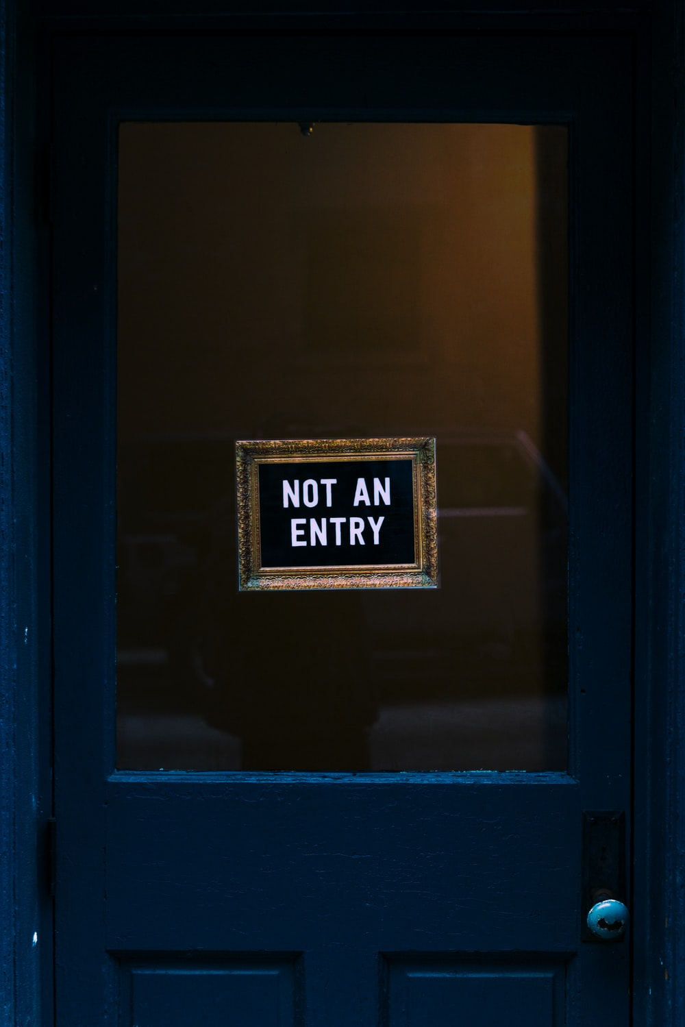 blue wooden door with not an entry signage
