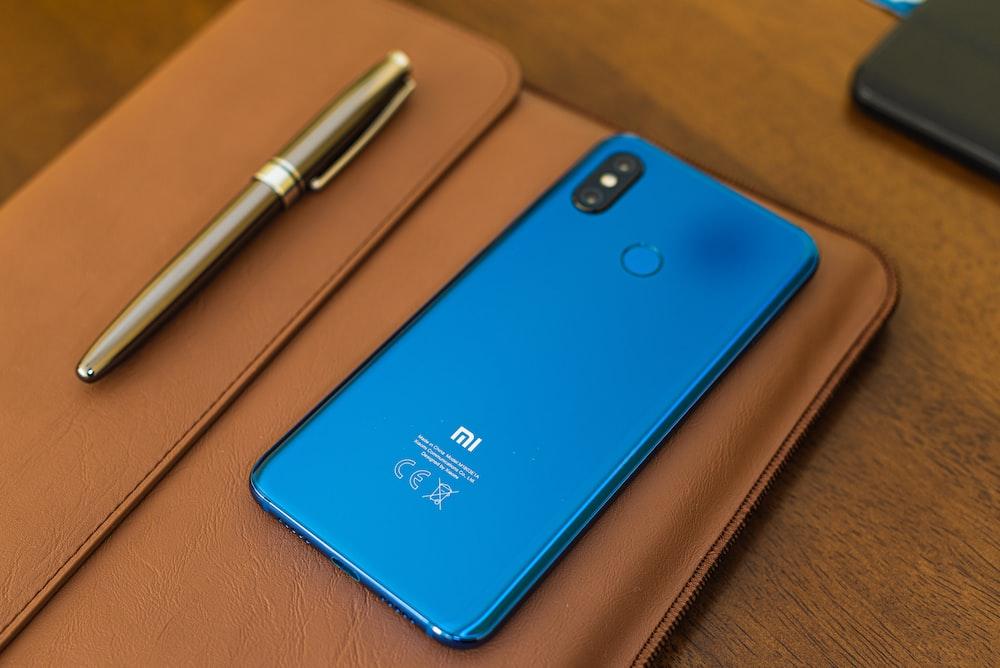 shallow focus photo of blue Xiaomi smartphone