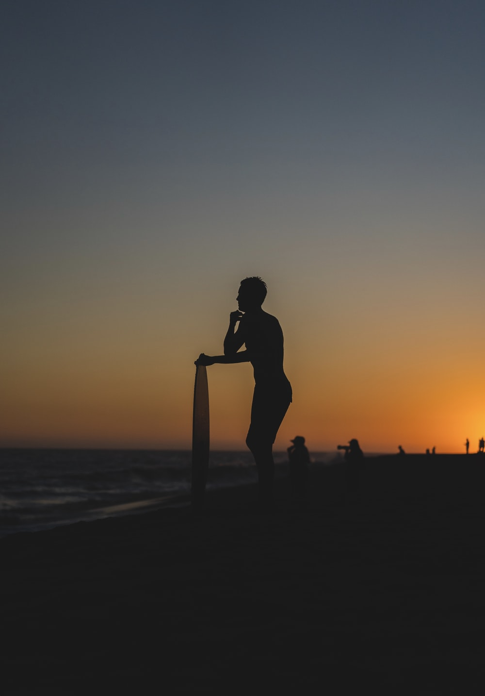 person standing and holding surfboard on shore during golden hour