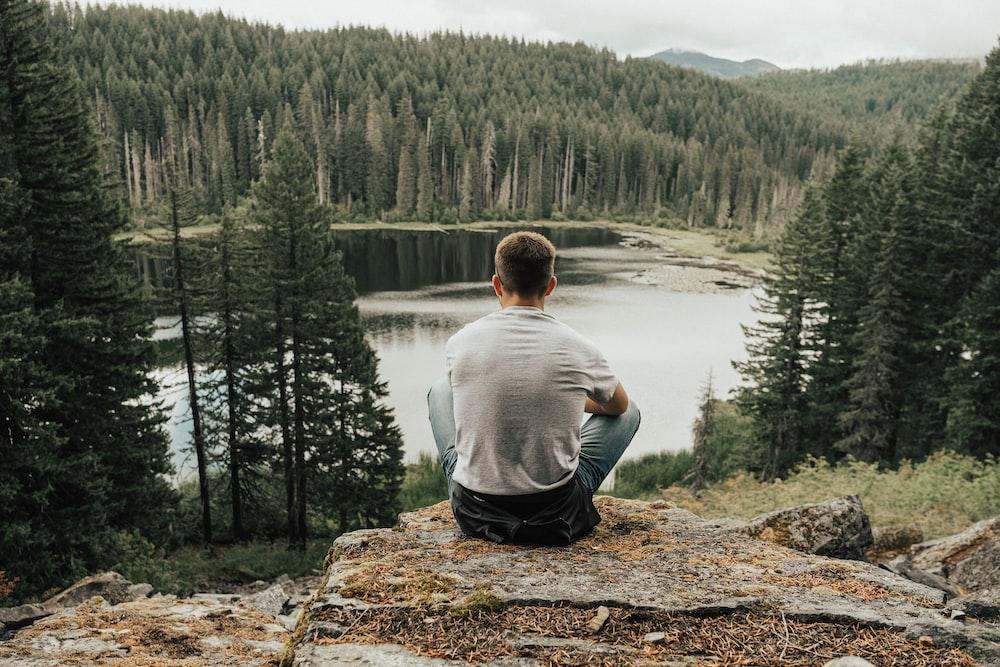 man sitting near lake
