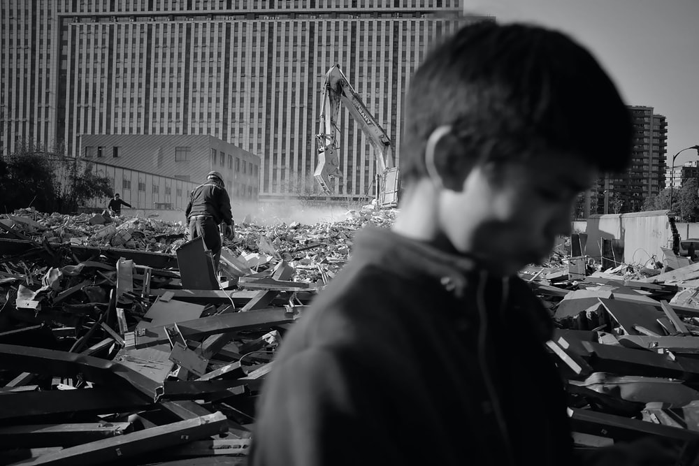 grayscale photography of person on demolished building