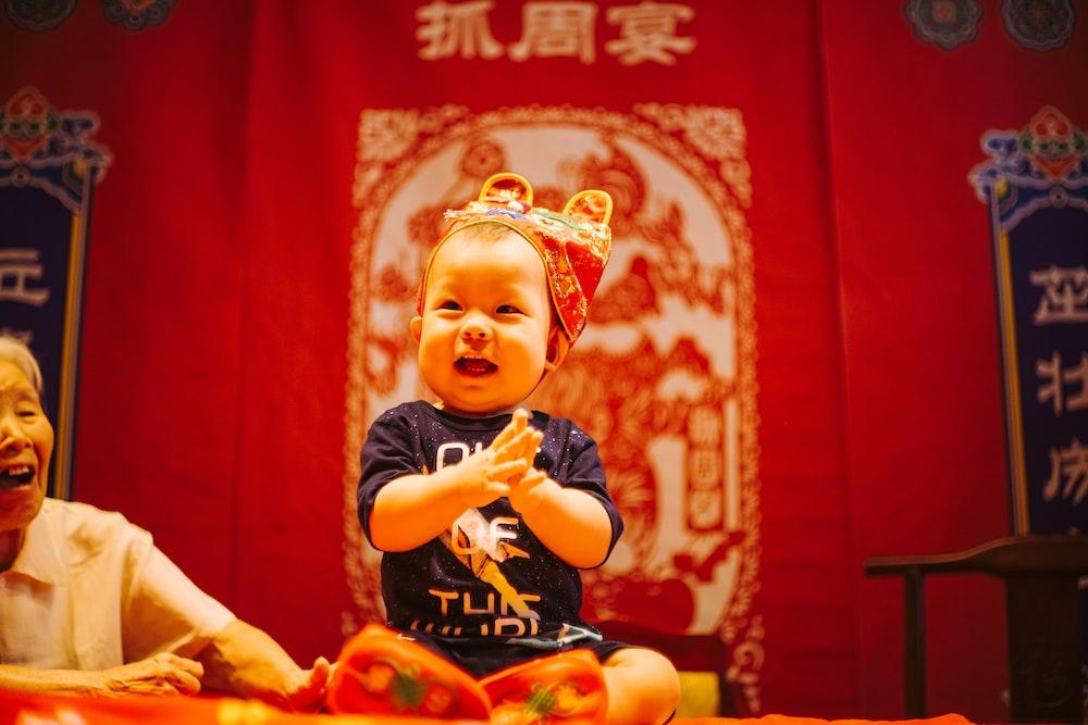 baby wearing blue shirt while smiling