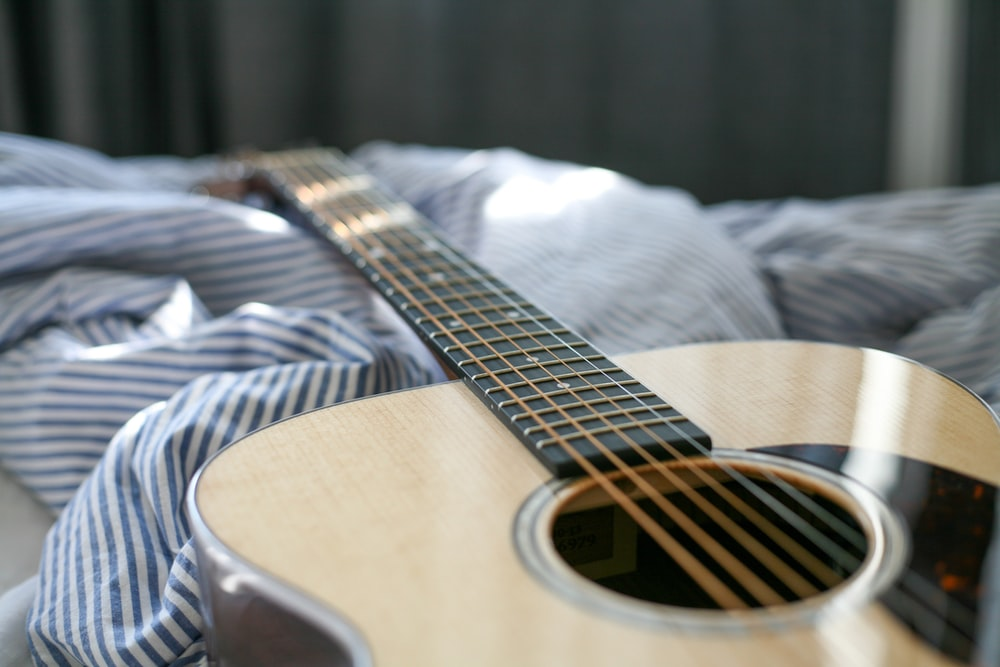 acoustic guitar on bed