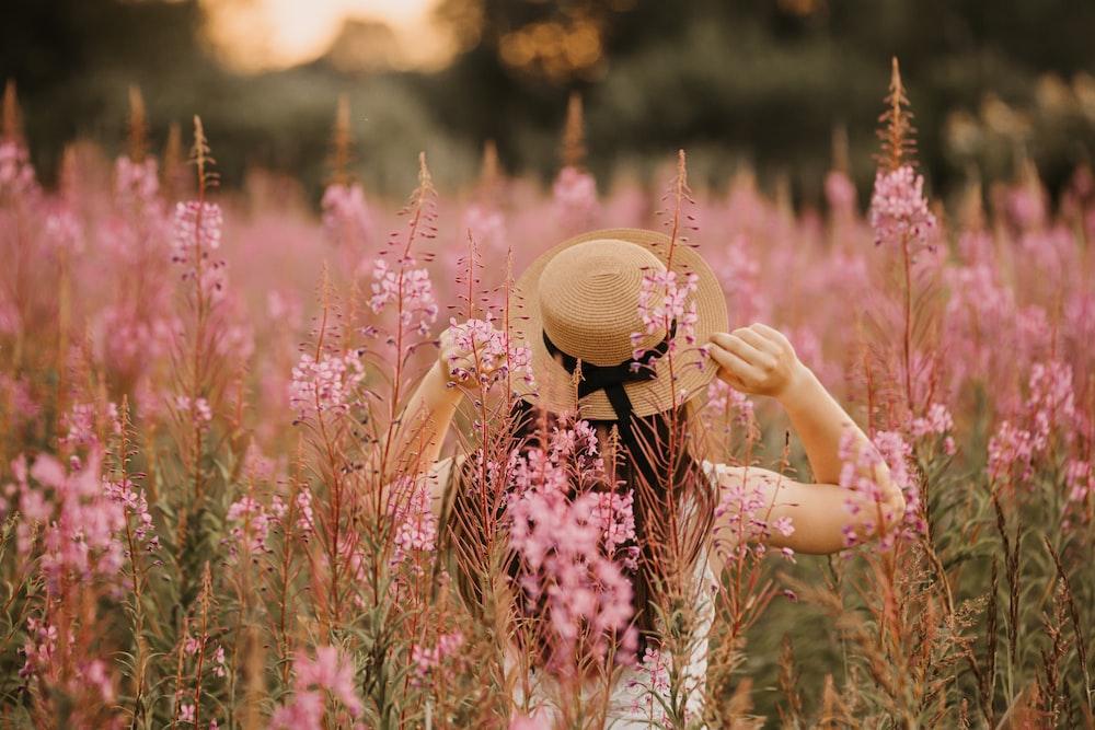 woman in white top on pink flower field