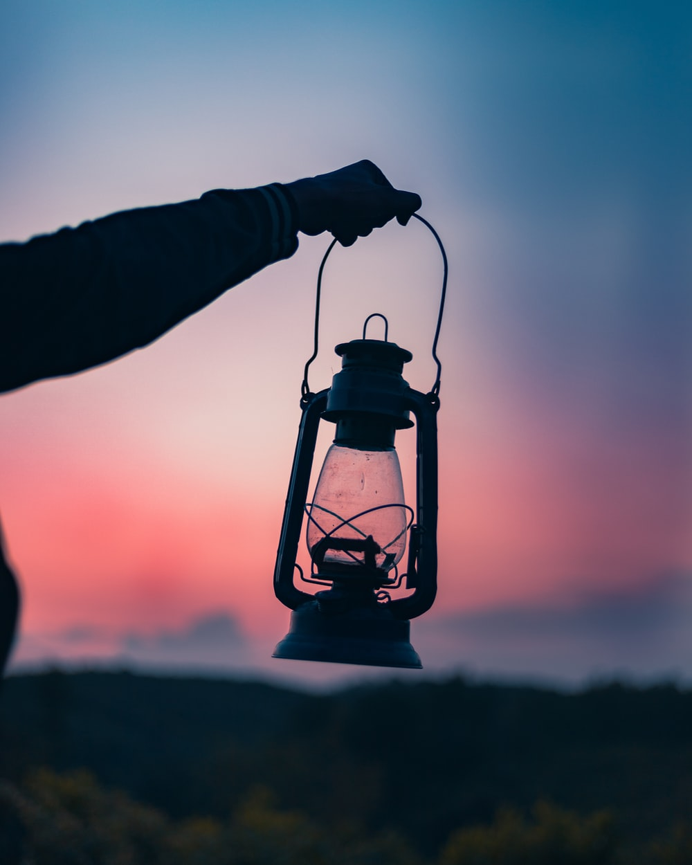 person holding gray gas lamp