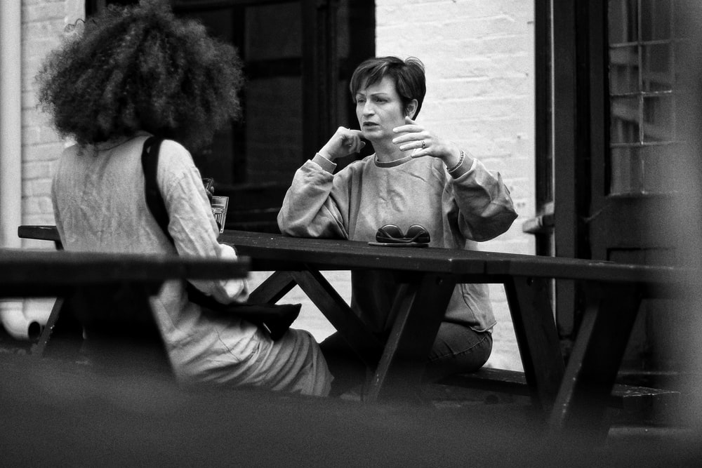 grayscale photo of two women sitting on bench