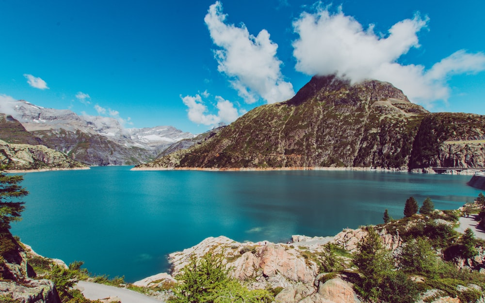 lake viewing mountain under blue and white skies during daytime