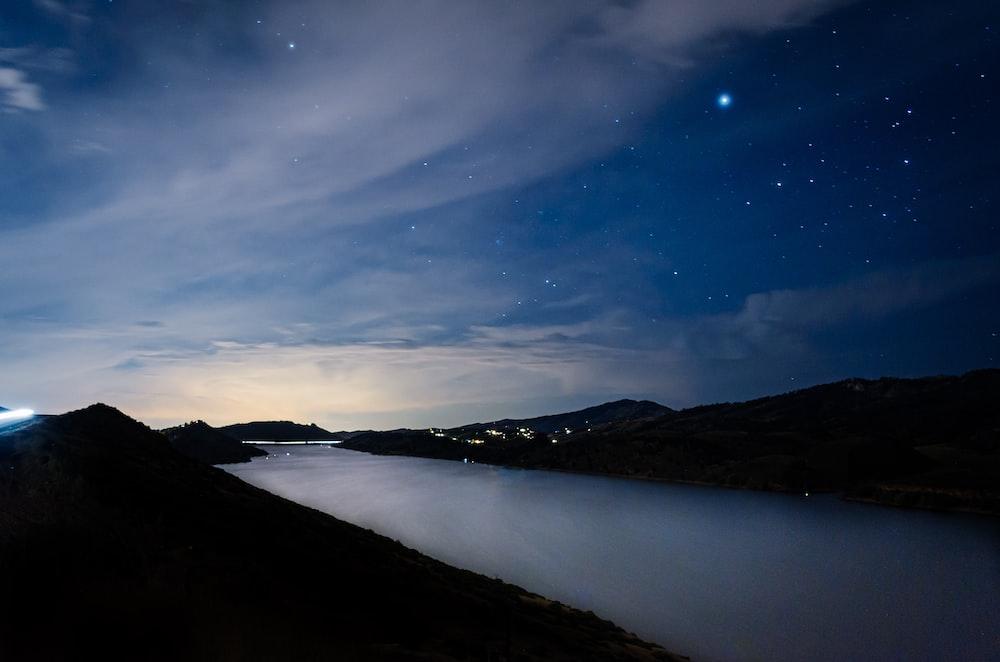 mountain near body of water at night
