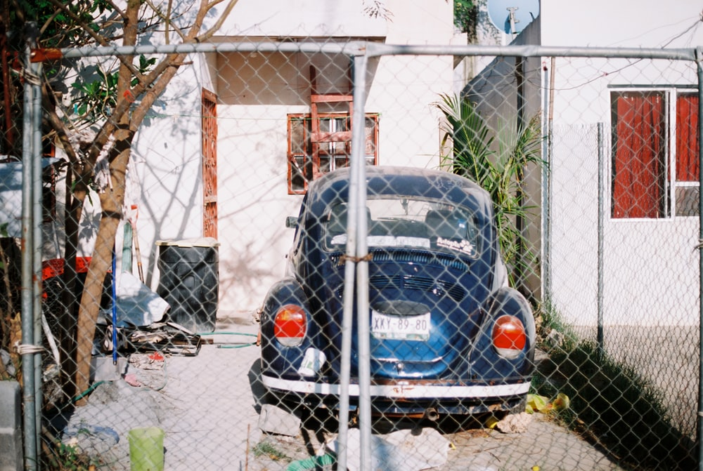 blue Volkswagen Beetle parked during daytime