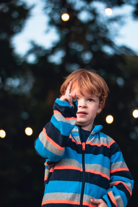 boy wearing multicolored striped zip-up jacket