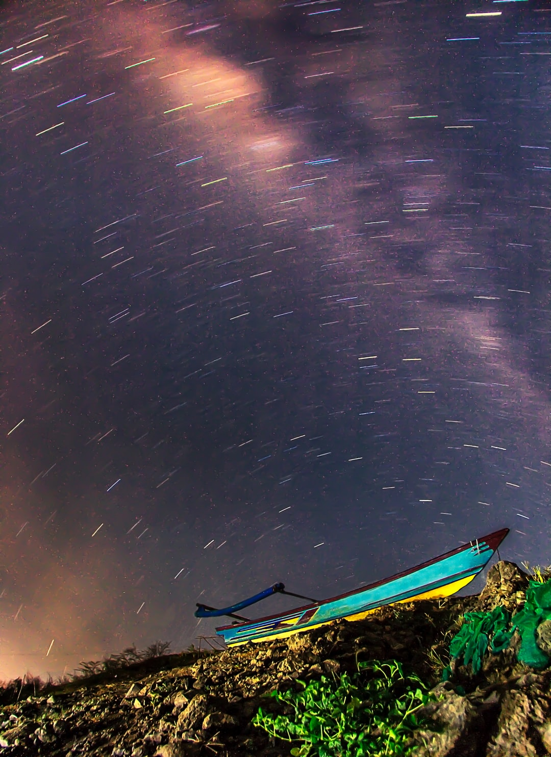 Display of the Star trails and Milky Way Galaxy that appears above that boat. Long exposure photography