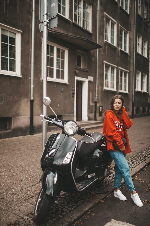 woman wearing orange pullover hoodie leaning on motorcycle