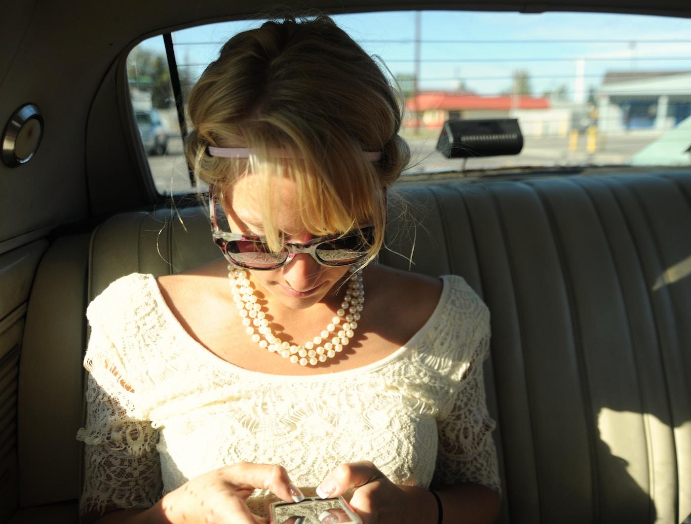 AdInMo. woman wearing white scoop-neck top inside vehicle