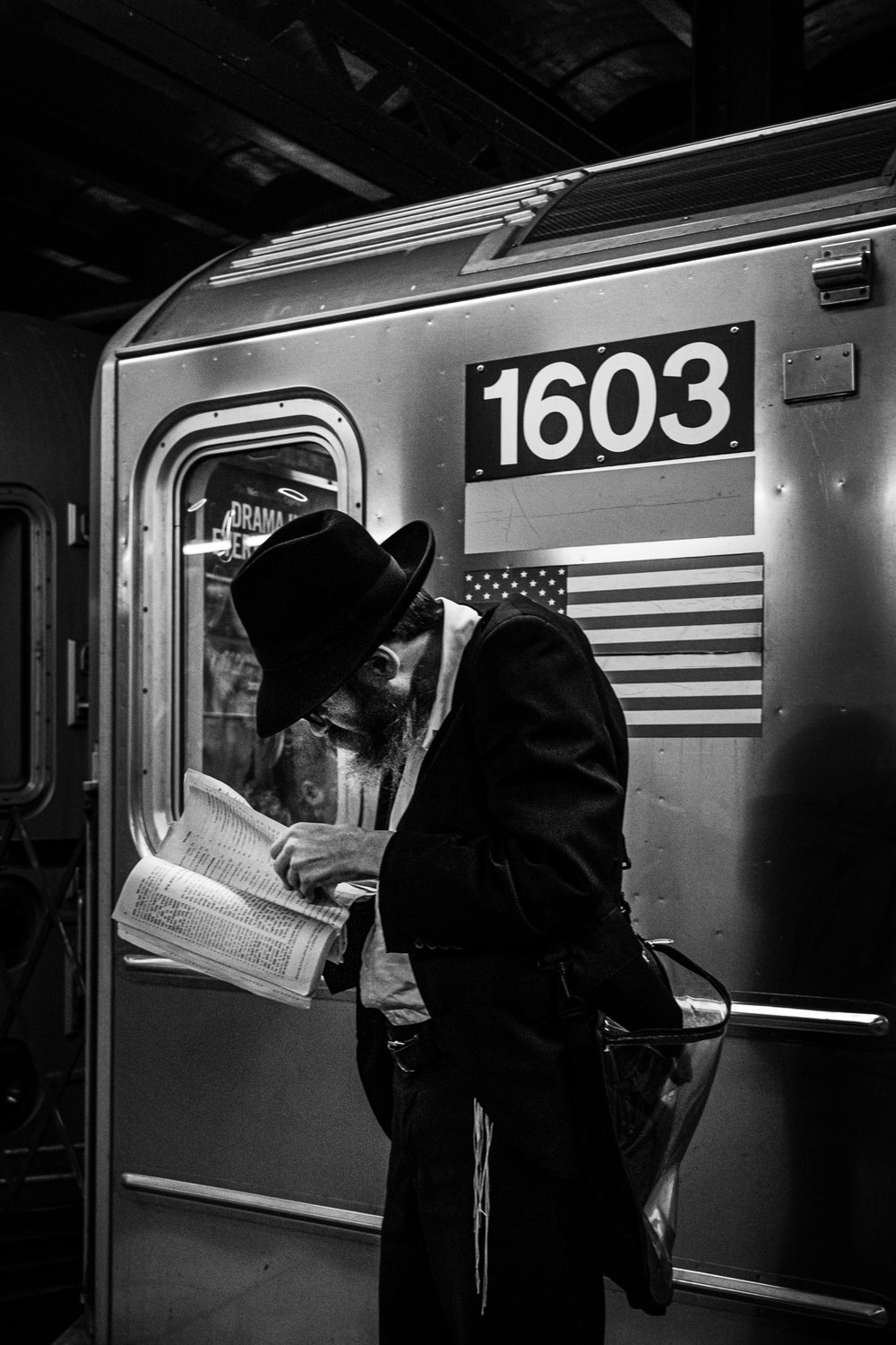 grayscale photo of man reading book beside train