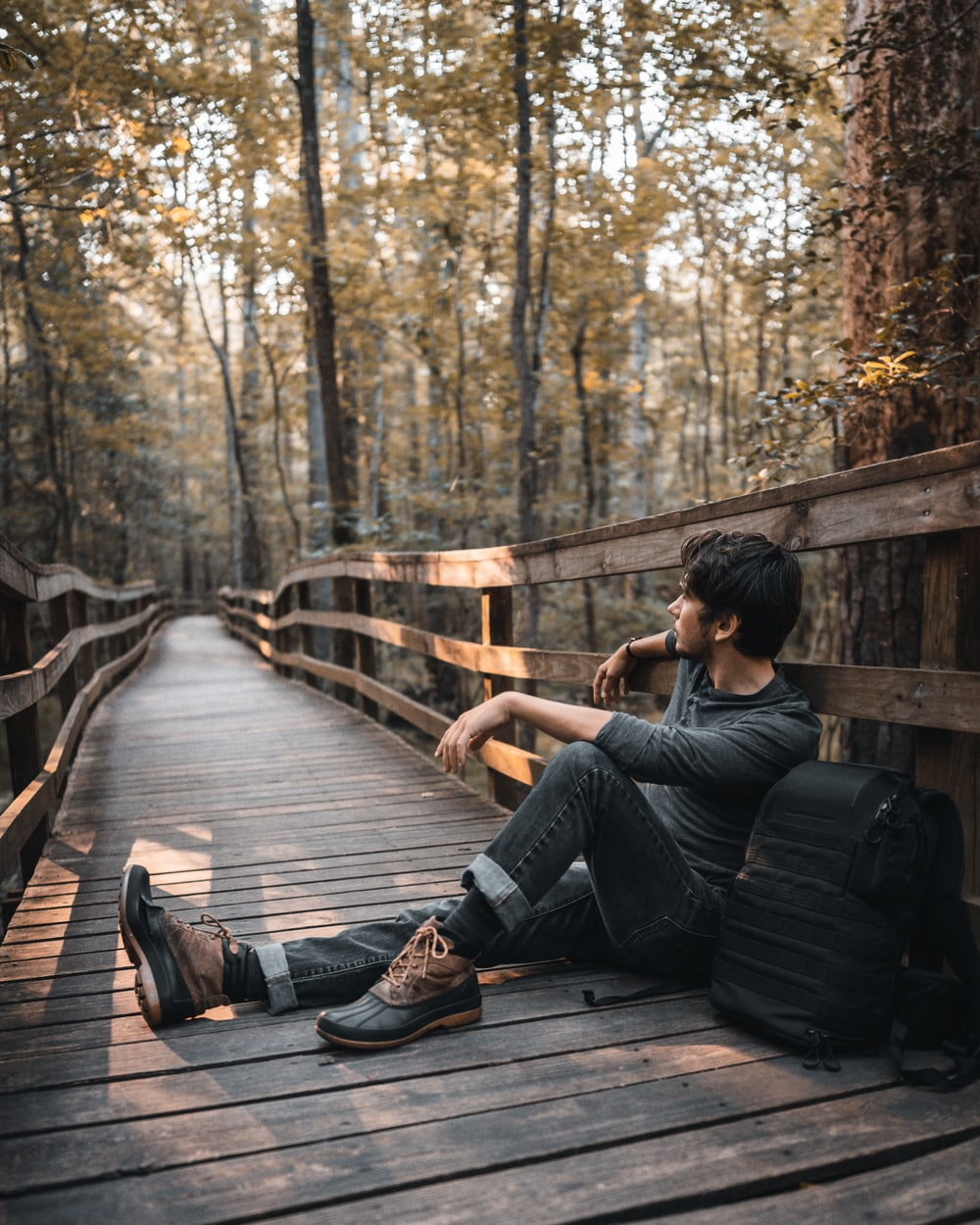 man sitting on wooden bridge