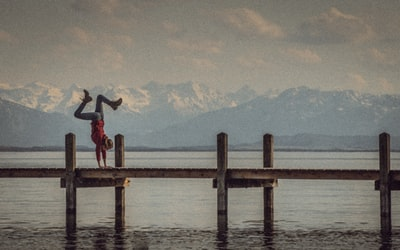 A girl performing a handstand in front of the mountains at Lake Starnberg, Germany