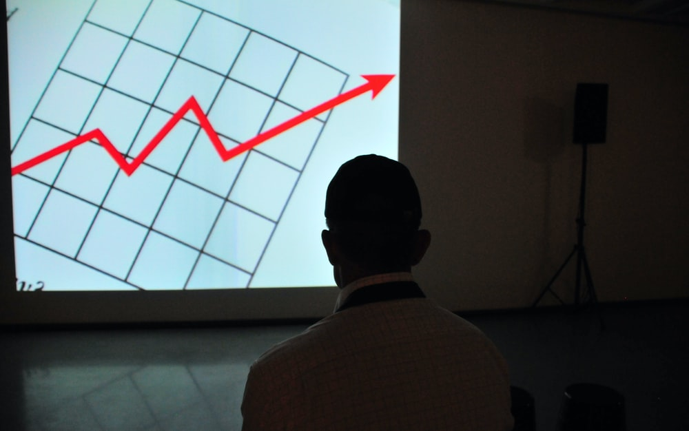 man wearing white top looking at projector graph screen