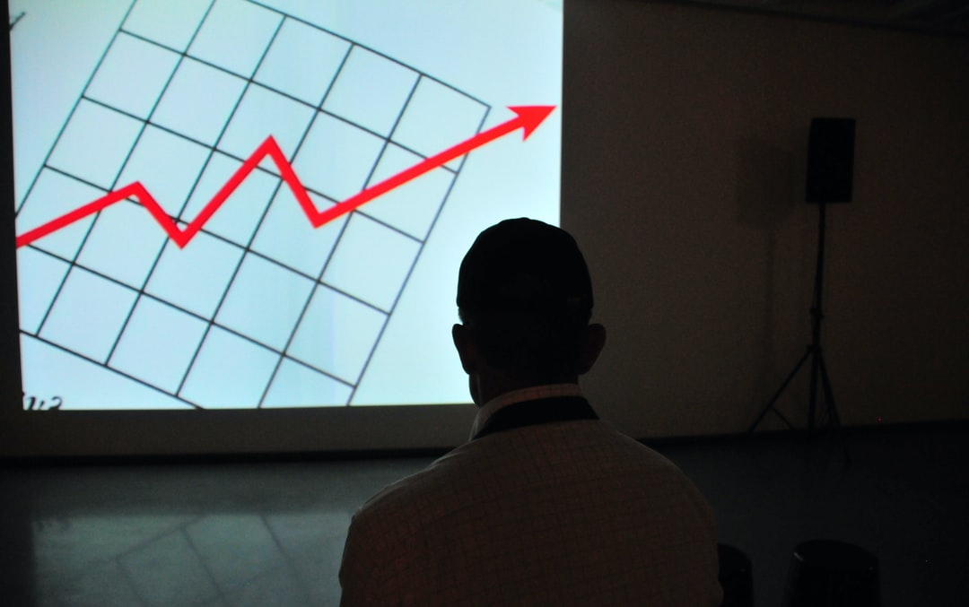 man wearing white top looking at projector graph screen of digital marketing analytics.