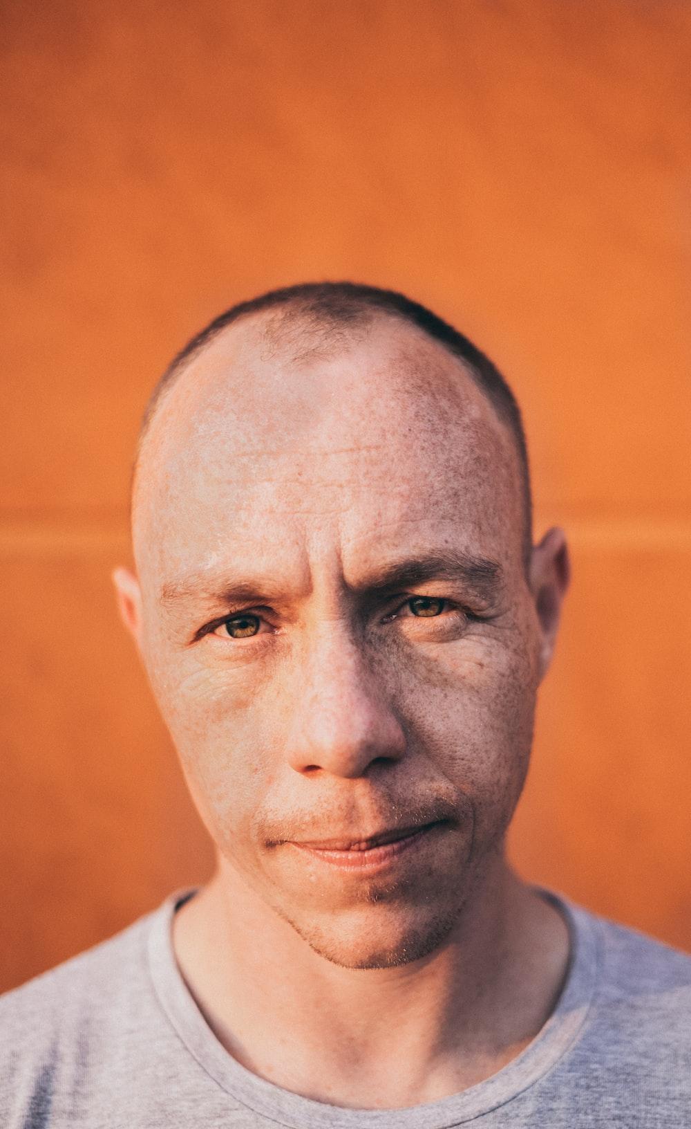 portrait of man wearing gray crew-neck shirt
