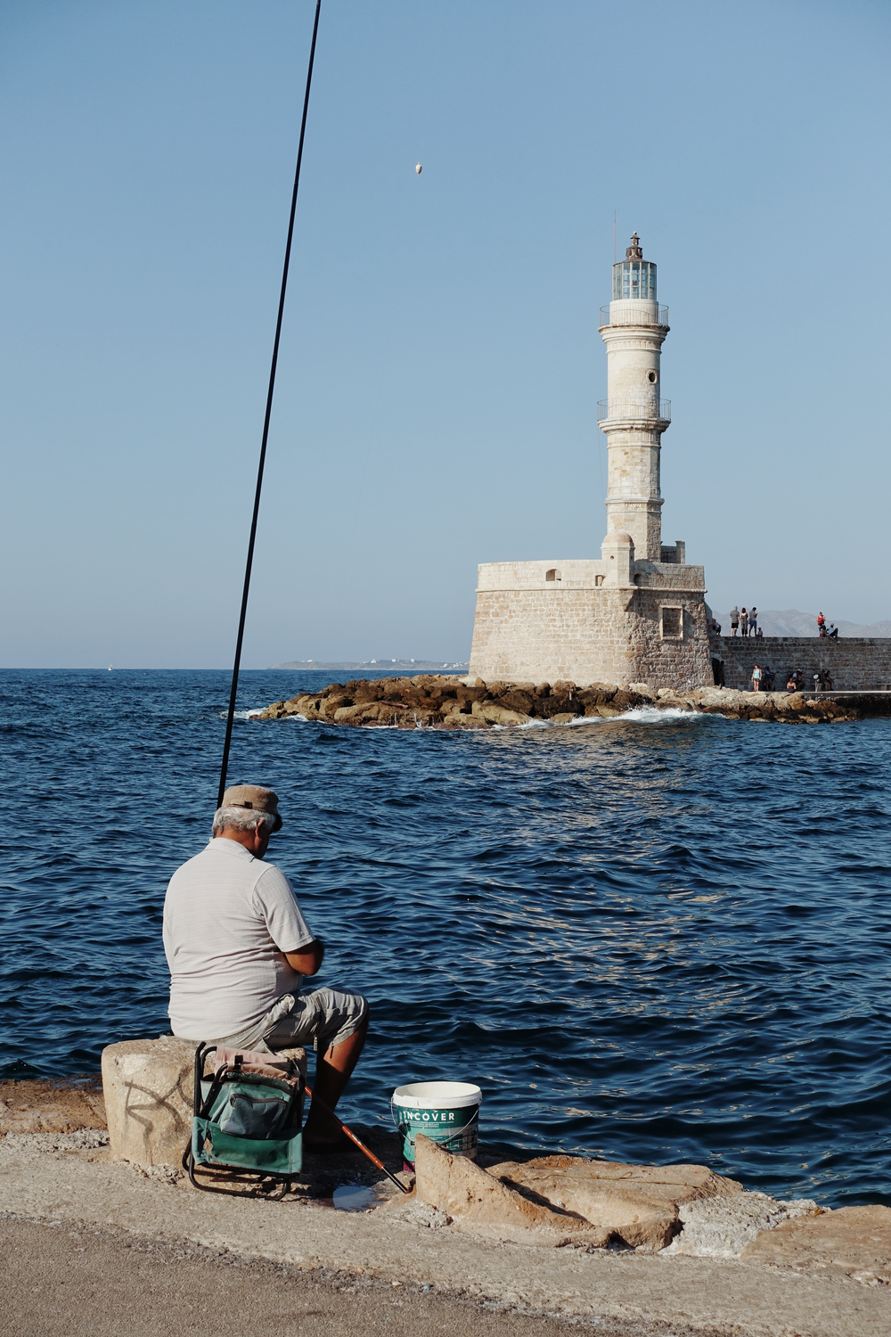 white stone lighthouse and a man fishing