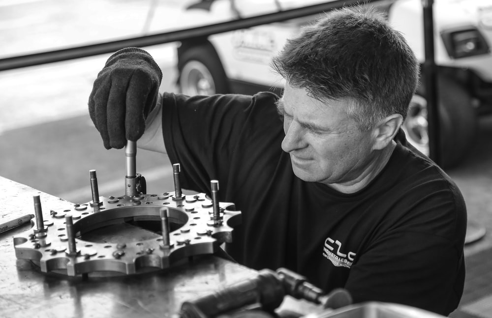 grayscale photo of man fixing gear