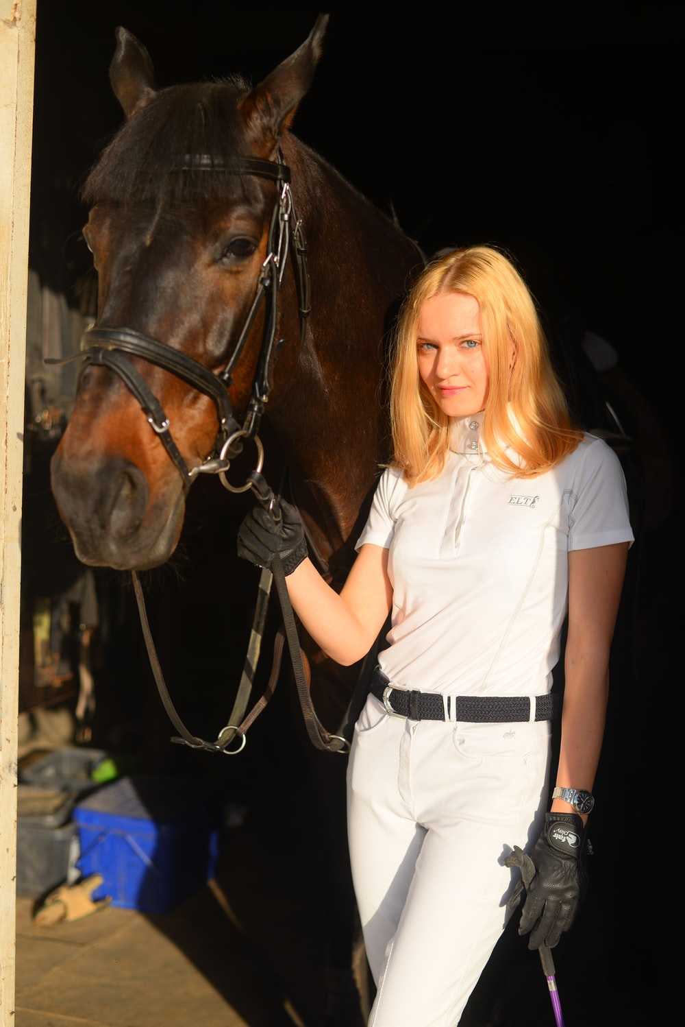 woman in white top standing beside brown horse