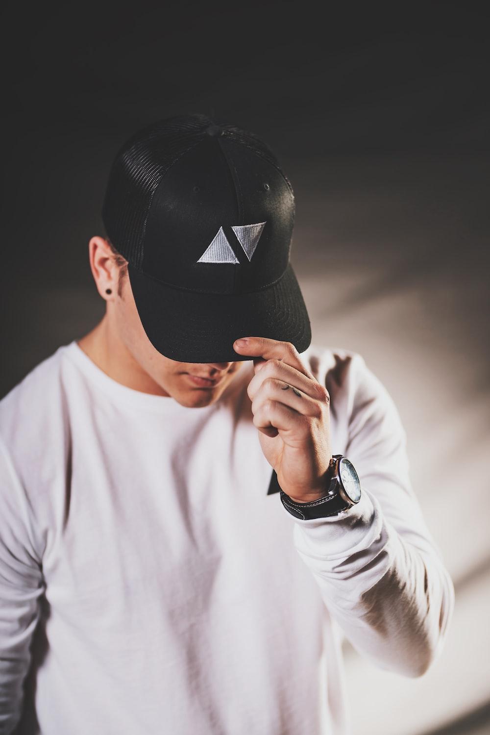 man wears black fitted cap