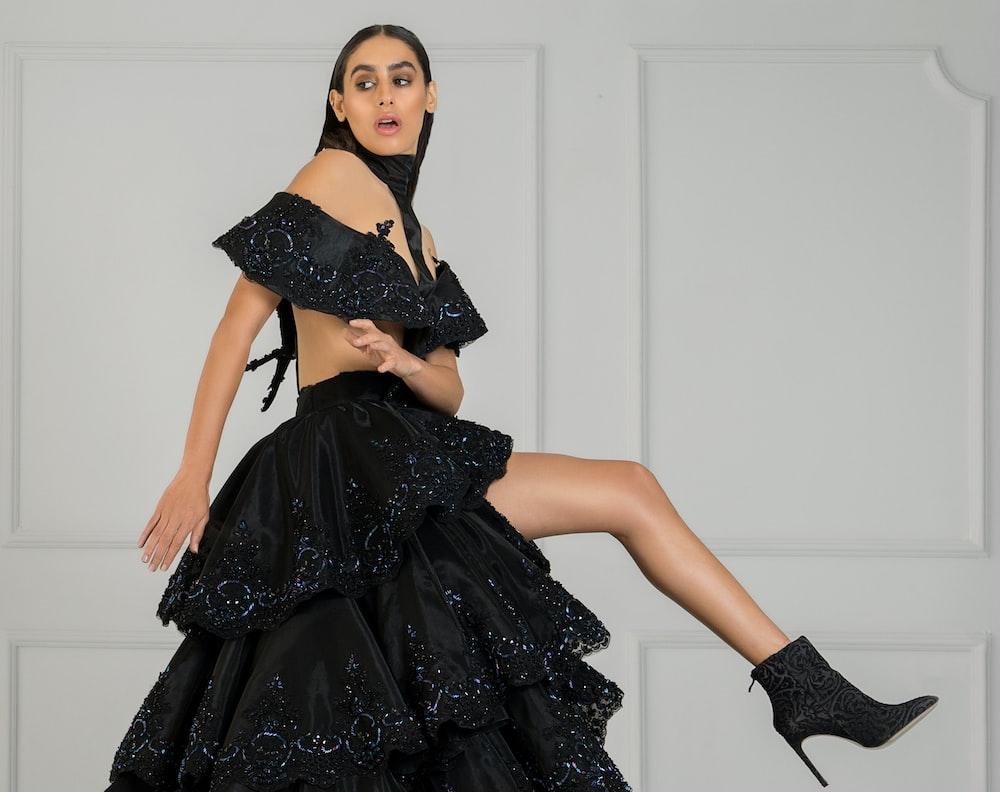 woman in black off-shoulder dress beside wall