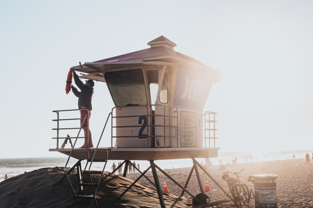 man standing on life guard post
