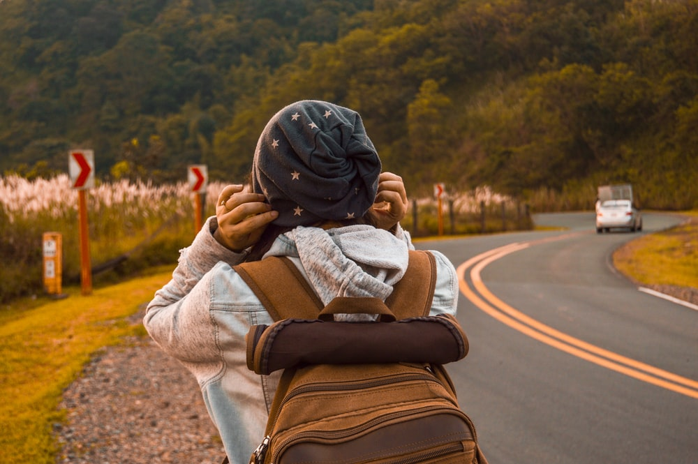 person carrying brown backpack close-up photography