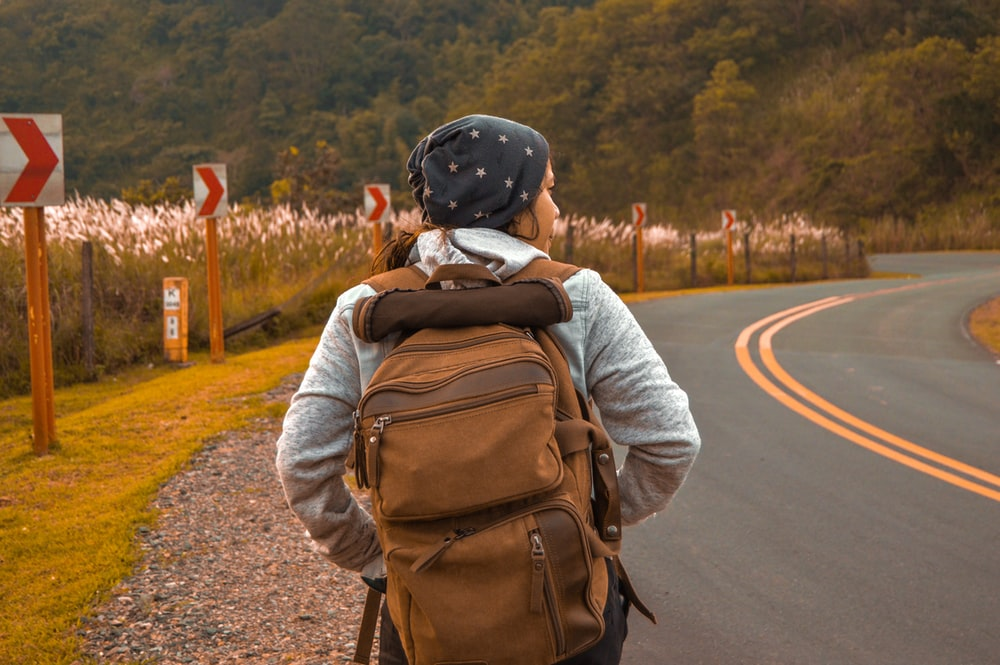 woman with brown backpack beside road