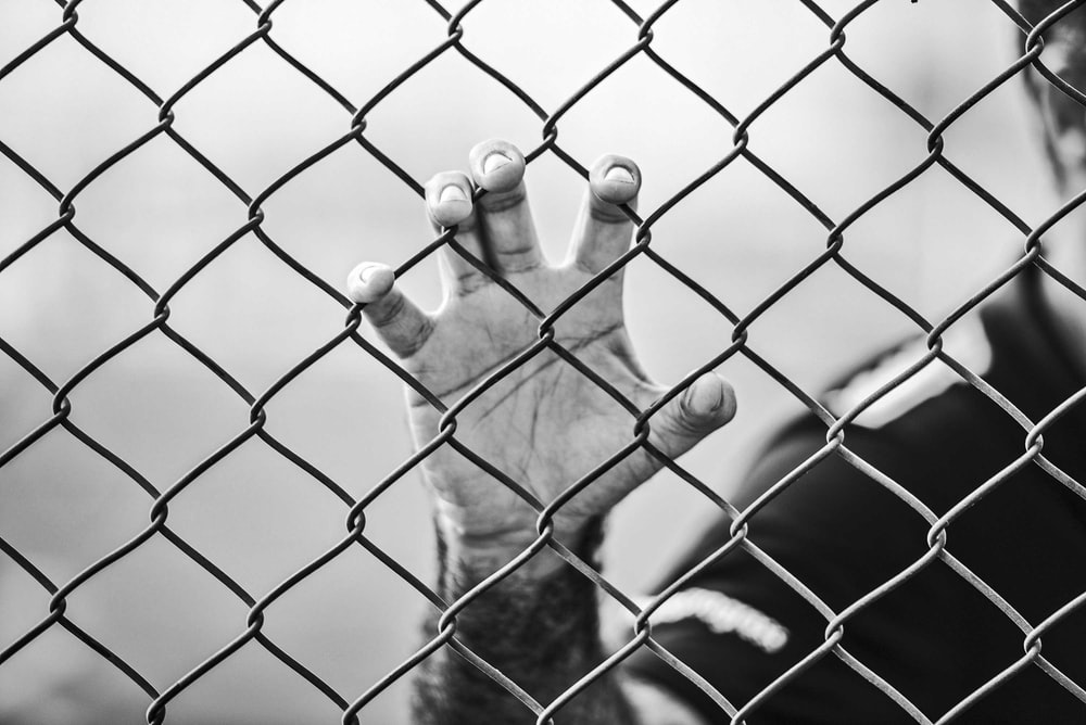 man holding chain-link fence