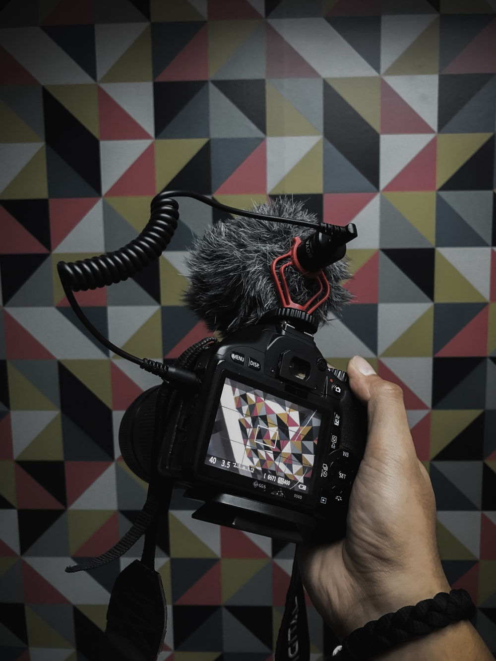 person holds DSLR camera with stereo recording cardioid microphone