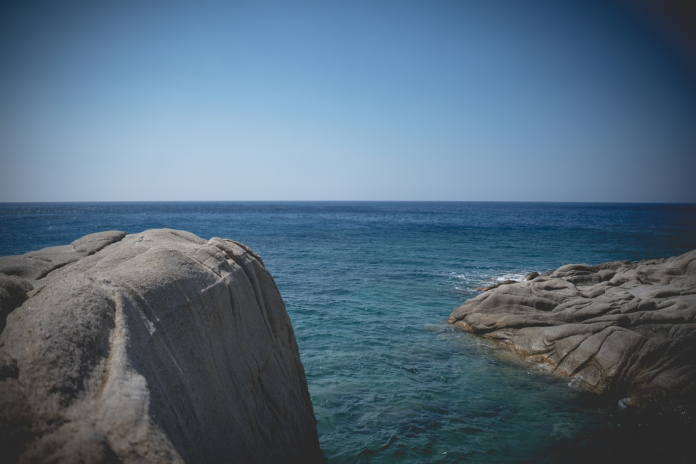 gray rock formation beside blue sea under blue sky during daytime