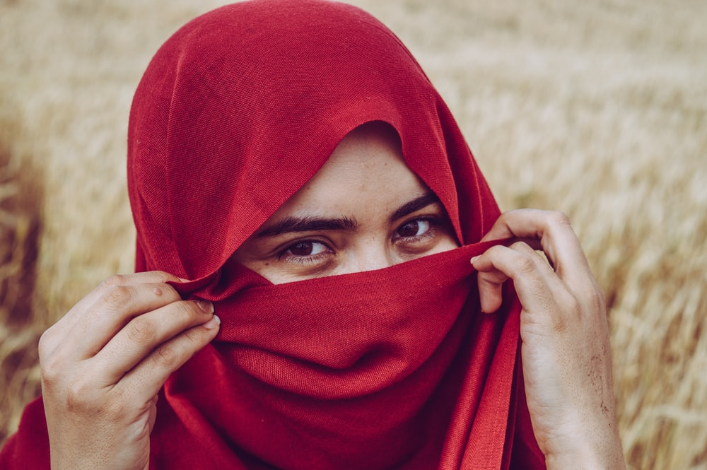 woman covers her face with red scarf