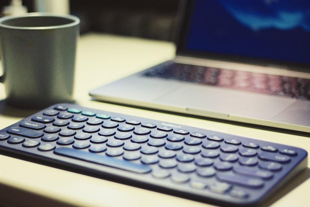 blue keyboard beside laptop