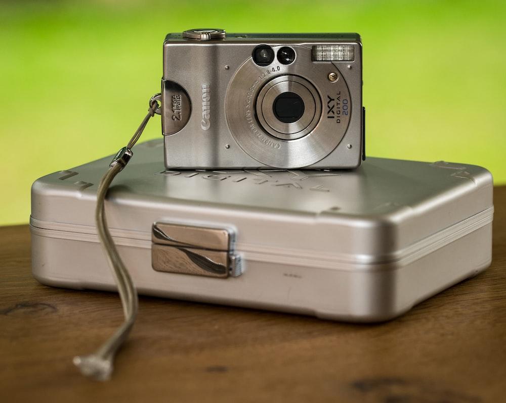 silver Canon compact camera on gray hardside case
