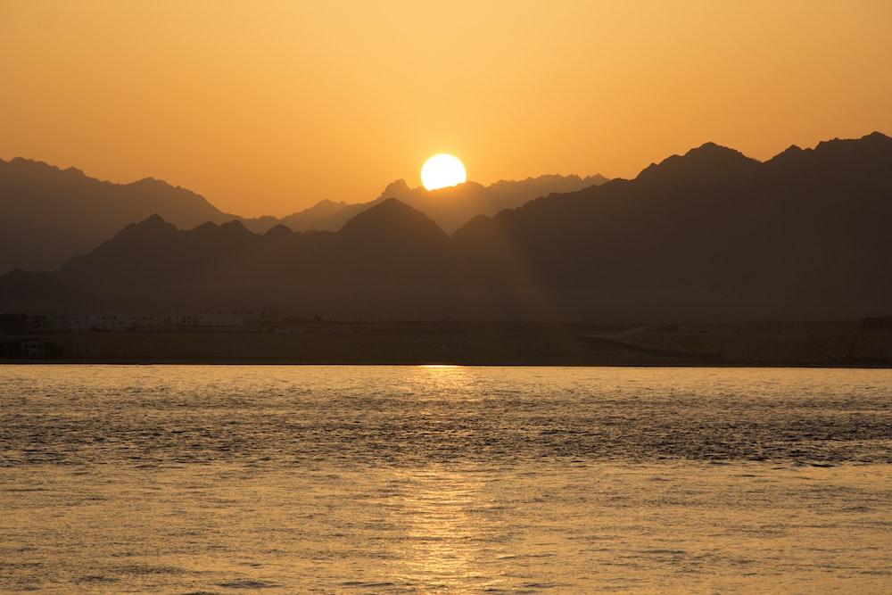 silhouette of mountain under sunrise