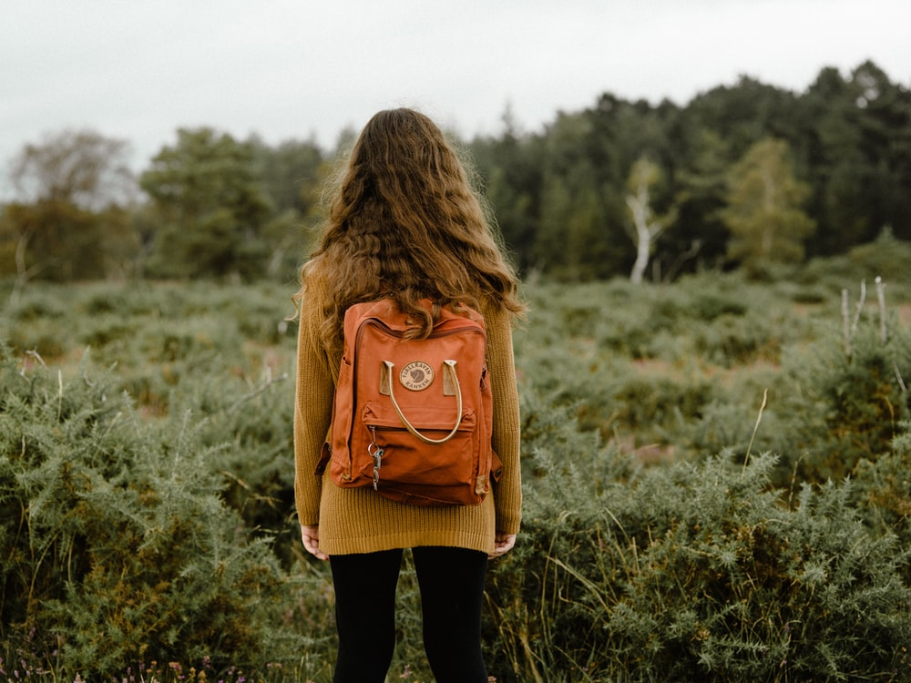 woman carrying backpack standing on grass during day