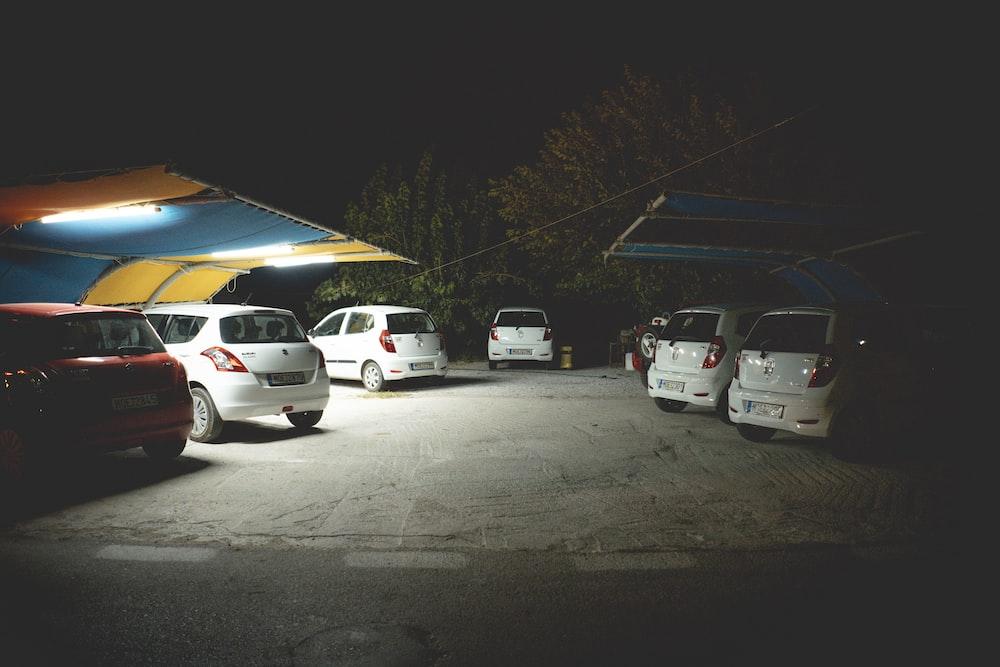 several vehicles parked beside sheds