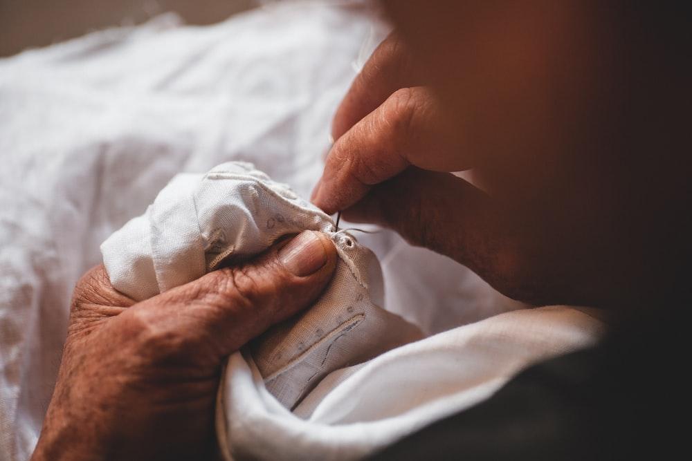 person sewing shirt