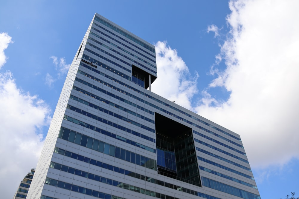 high-angle photography of high-rise building under blue and white skies during daytime