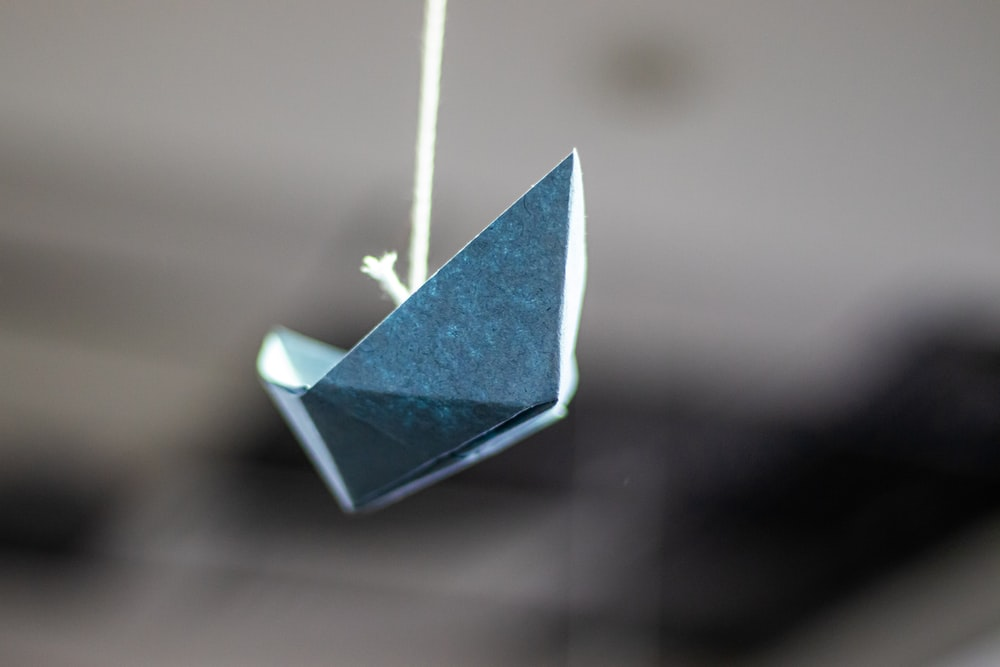 macro photography of blue paper boat