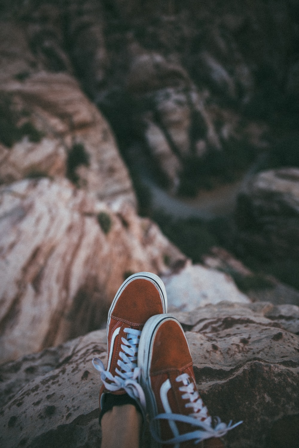 person sitting on cliff wearing brown-and-white Vans low-top sneakers