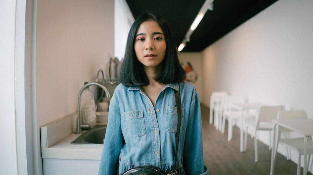 women's in blue denim button-up long-sleeved shirt