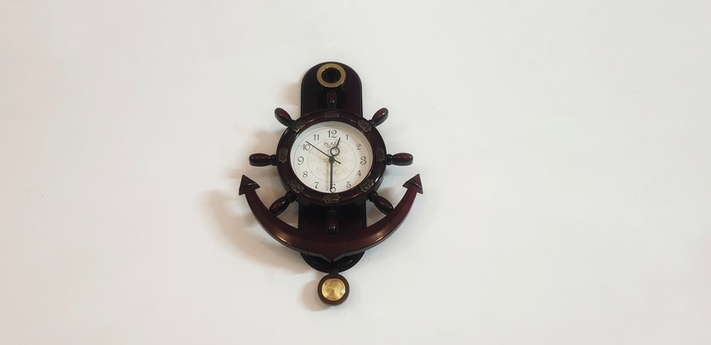 brown wooden anchor frame analog pendulum clock