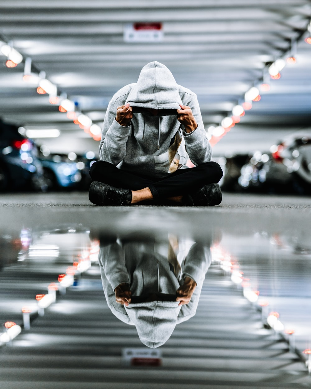 person sits while wearing hoodie