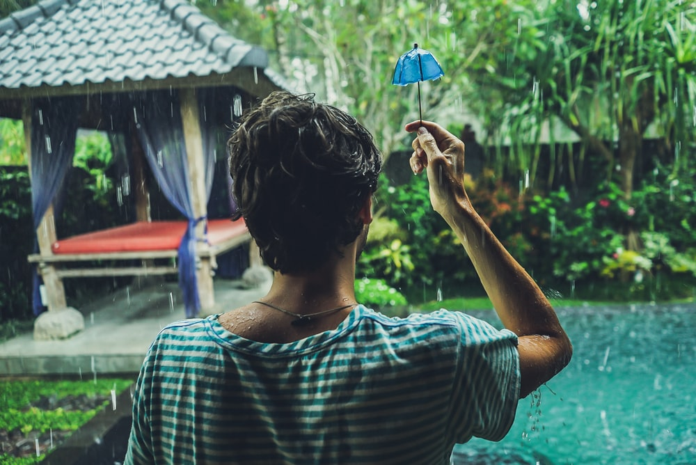 man holding blue umbrella miniature facing the pool during rain