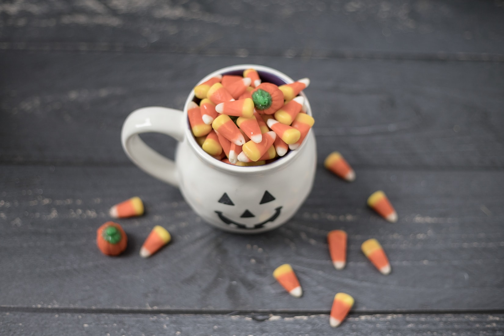 Pumpkin Halloween mug with candy corn on wood background.