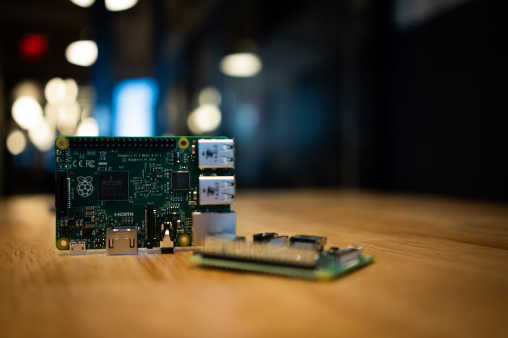 two green circuit boards on wooden surface
